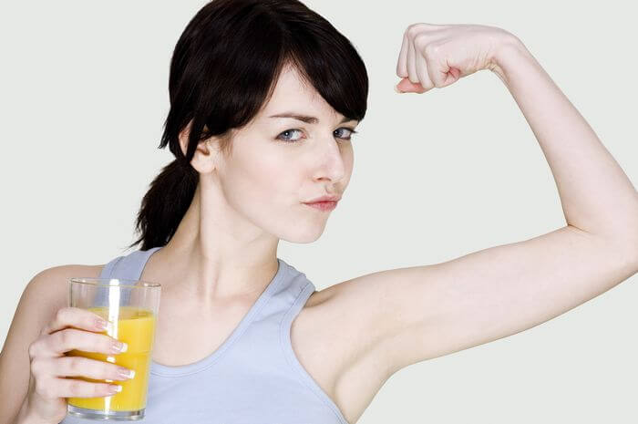 Woman drinking juice and feeling energetic by flexing her arms.