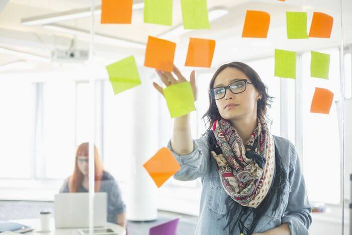 Woman placing sticky notes on a glass wall and planning for the future.