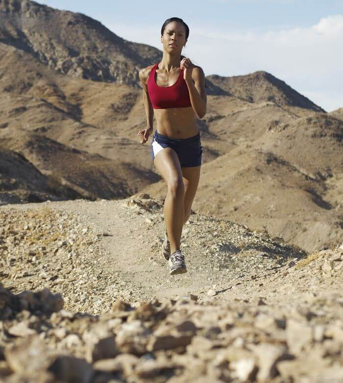 Slim and fit woman running in the hills.