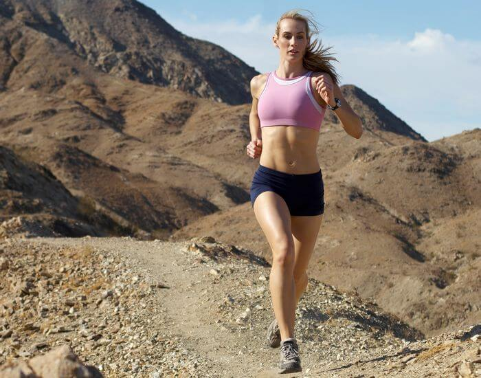 Fit, slim woman with low body fat ratio running with hills in the background