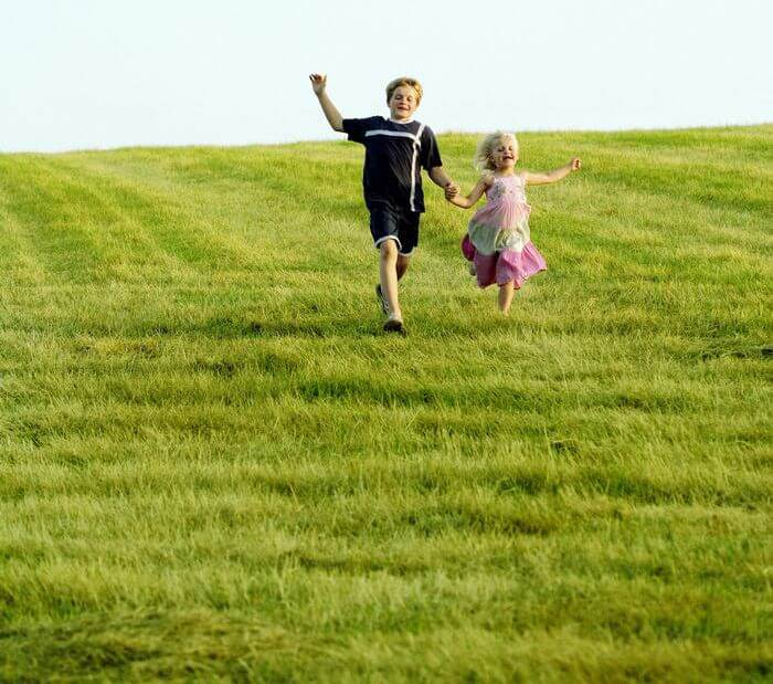 Children running down hill on a lush green meadow.