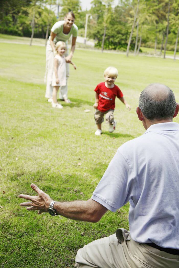 Senior man playing with his grand children, while the children are running in a park.