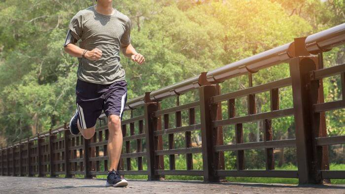 Healthy, athletic man running on a bridge with green trees and plants in the background.