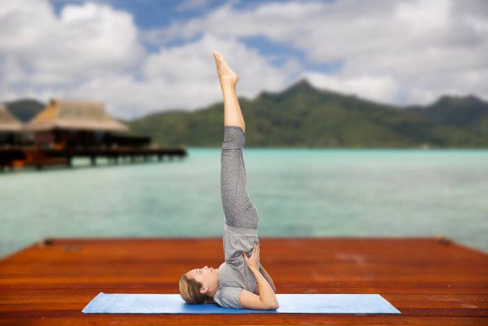 Woman in Shoulder Stand Pose (Sarvangasana). Scenic Background with Lake and Mountain in Backdrop.