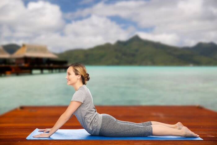 Woman in Cobra Pose (Bhujangasana). Scenic Background with Lake and Mountain in Backdrop.