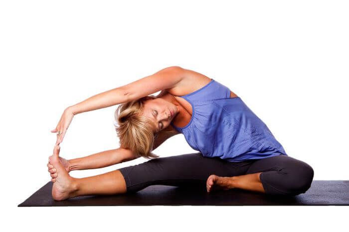 Woman in Head-to-Knee Pose (Janu Sirsasana).