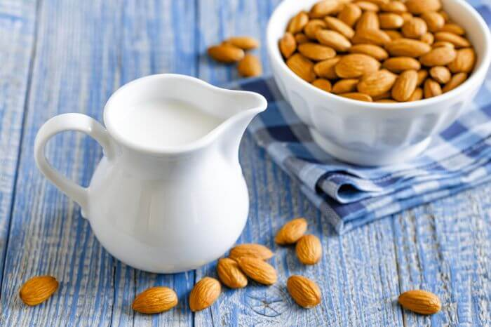 Almond milk in jug with almonds lying on table