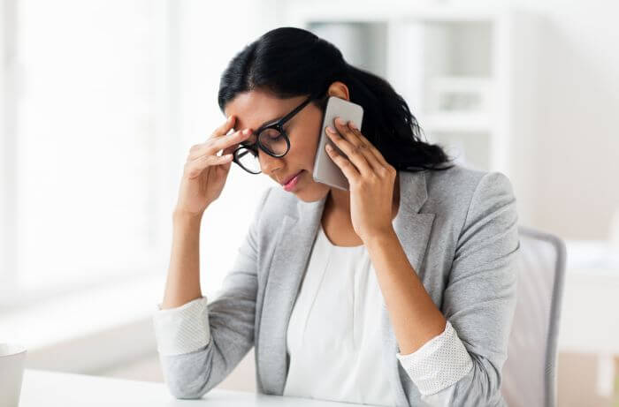 Women with a hand on forehead seems stressed and anxious.