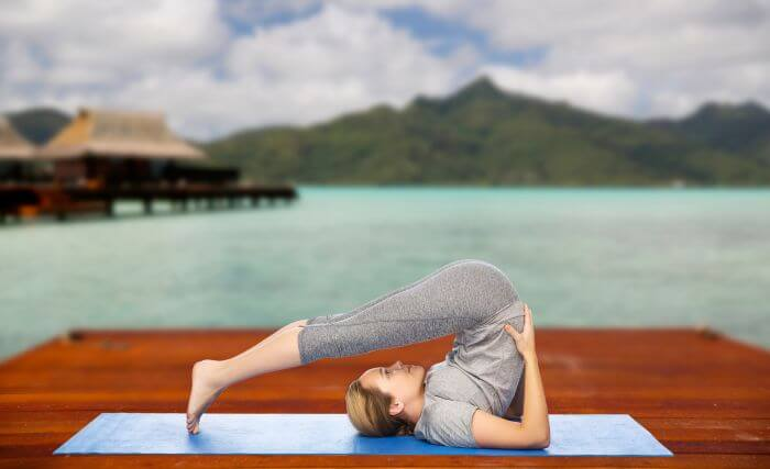 Woman in Plough Pose (Halasana). Scenic Background with Lake and Mountain in Backdrop.