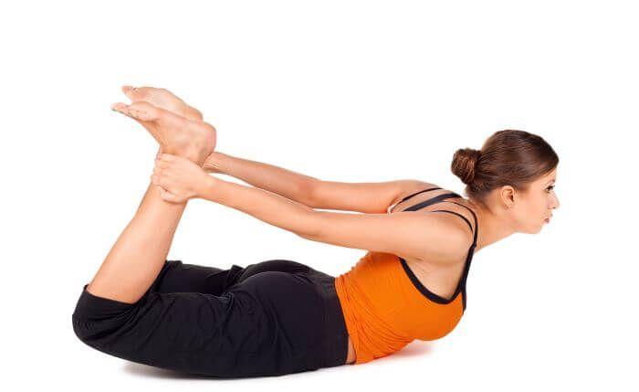 Woman doing Yoga - Bow Pose (Dhanurasana)