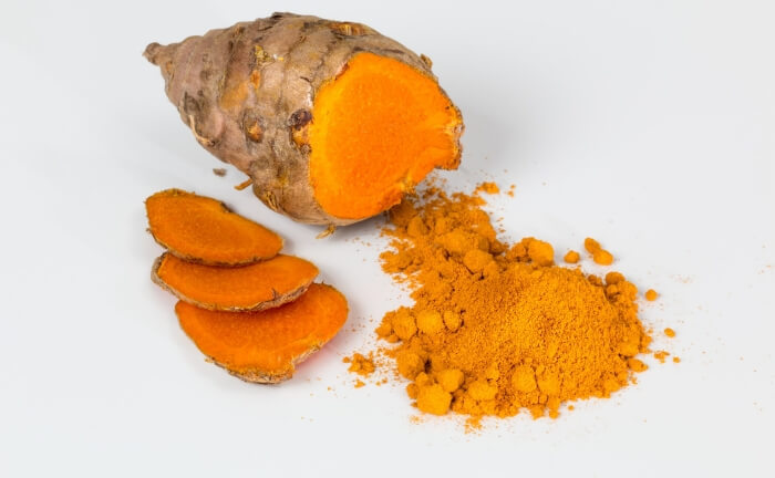 Turmeric root lying on white background, with turmeric root slices on the left side.