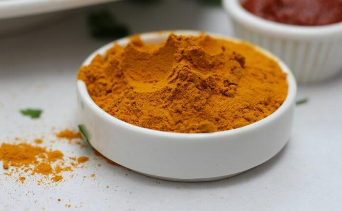 White bowl full of turmeric (haldi) powder.