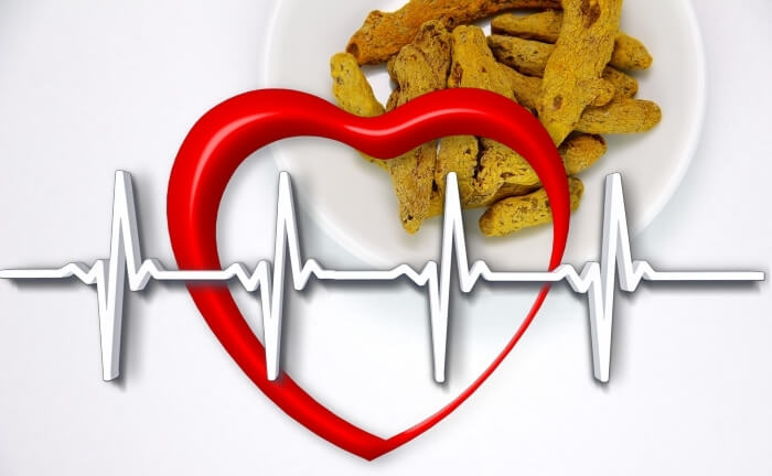 A healthy heart with healthy ECG graph, and dried turmeric sticks in a bowl in the background.