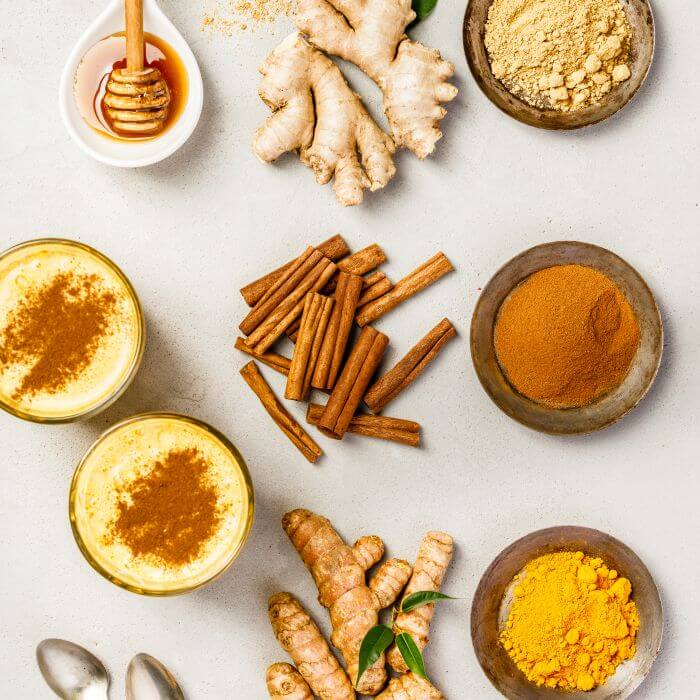 Herbs, spices and turmeric in glasses and bowls placed on a white background