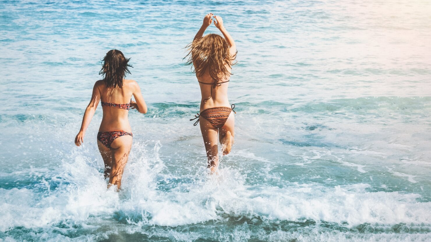 fit, good looking women with tonned up body running towrards the beach.